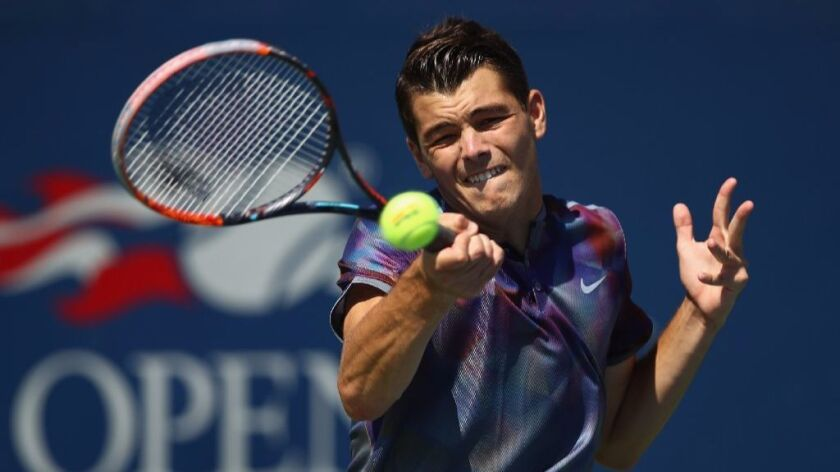 Taylor Fritz returns a shot to Marcos Baghdatis at the U.S. Open. Fritz won the match for his first