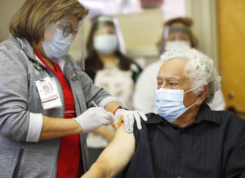 Carlos Alegre, 72, a resident of Birch Patrick Skilled Nursing Facility receives a COVID-19 vaccine shot