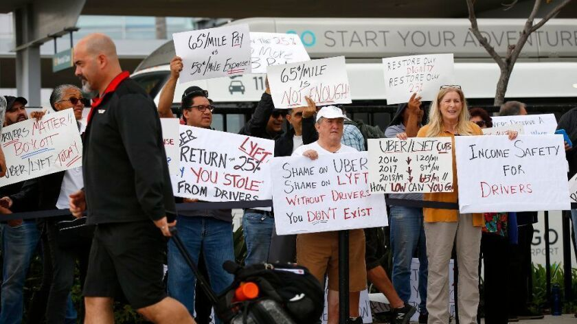 Uber and Lyft drivers picket at San Diego International Airport during a strike in May.