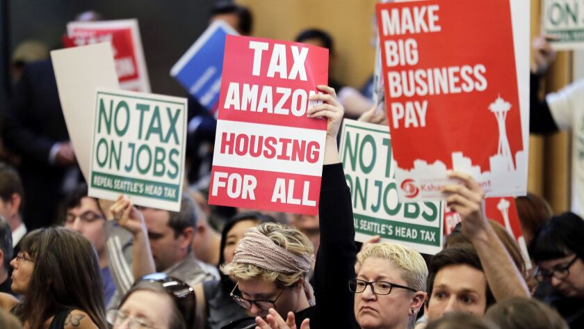 """People attending a Seattle City Council meeting hold signs that read """"Tax Amazon, Housing for All,"""""""
