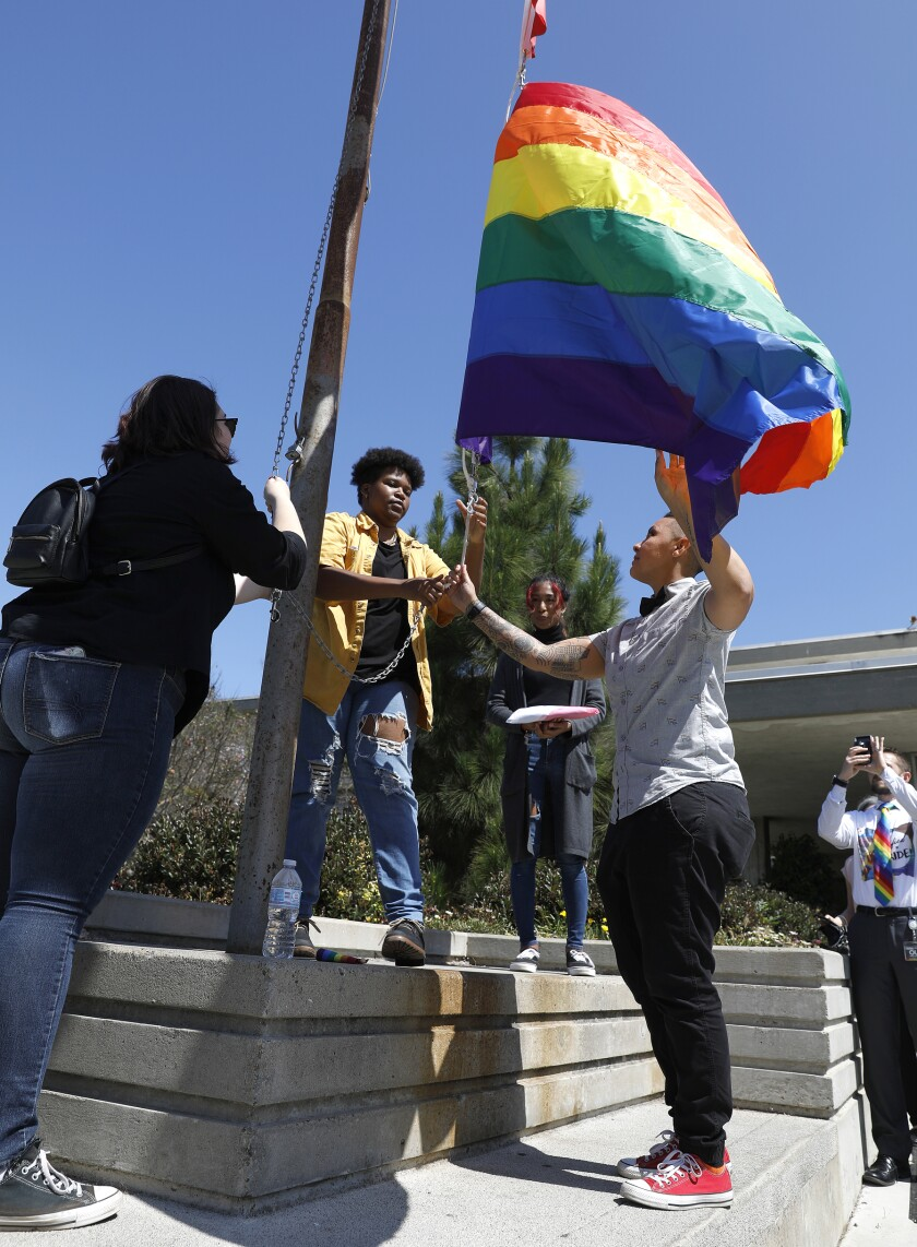 San Diego Unified School District Friday raised a pride flag and Trans flag at district headquarters for the first time in its history. Students Jay Sieber (left), Savion Morgan Cooper (center), Samsara Drapiza (background) and Ebonee Weathers, an SDUSD program manager (right) raised the LGBTQIA and Trans flags.