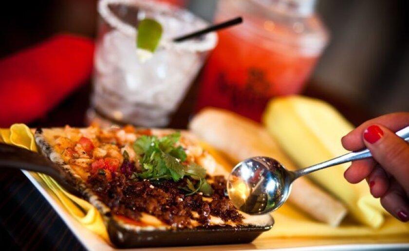 Miguel's Cocina does Queso Fundido Mar y Tierra, a sautéed Mexican shrimp, chorizo and salsa fresca dish.