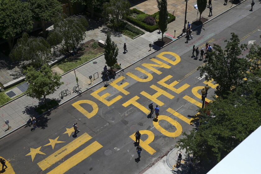 """""""Defund The Police"""" is painted in large, yellow block letters on the street"""