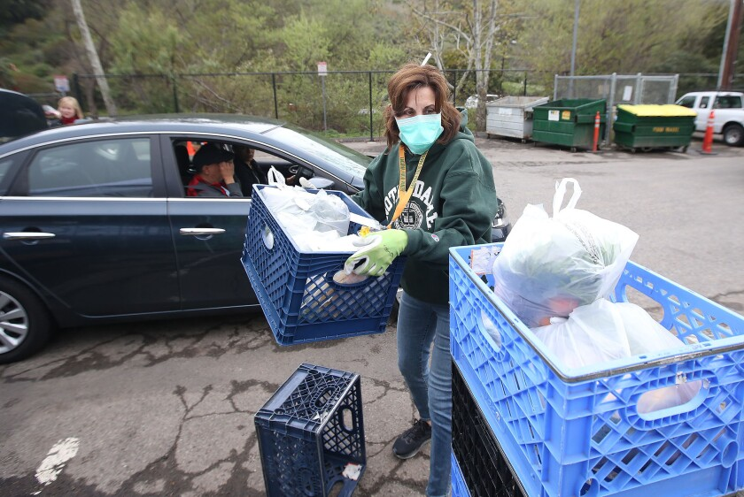 Volunteer Chris Etow loads containers filled with bags of groceries for a visitor outside the Laguna Food Pantry on Wednesday.
