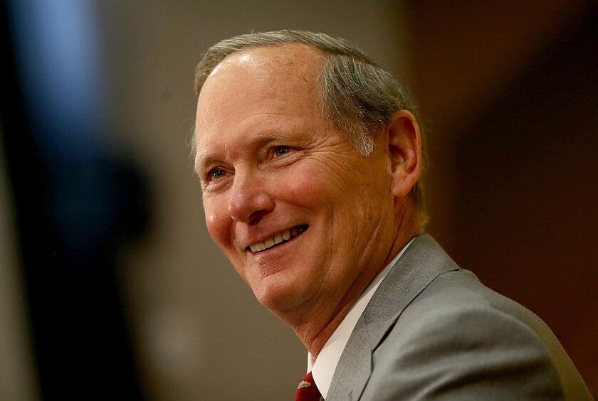USC Athletic Director Pat Haden smiles as he speaks during an introductory press conference for Coach Steve Sarkisian on Dec. 3, 2013.
