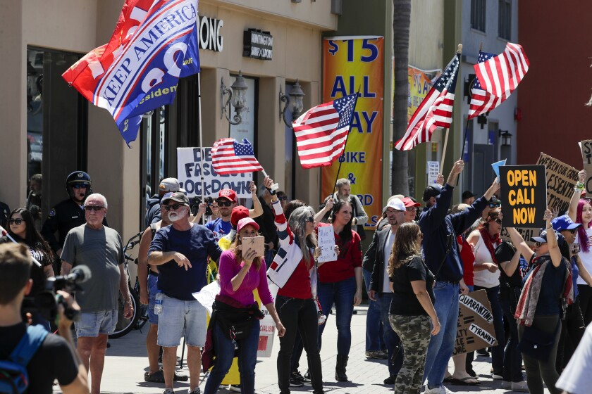 Supporters of President Trump rally against business closures due to the COVID-19 pandemic along Main Street in Huntington Beach.