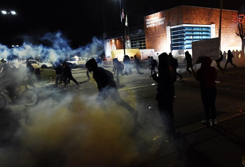Demonstrators outside Ferguson police headquarters flee police tear gas Monday night.