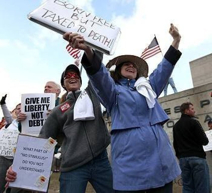Robin Smith of Rancho Penasquitos and Lori Necochea of Poway protest at the San Diego Midway post office building Wednesday.