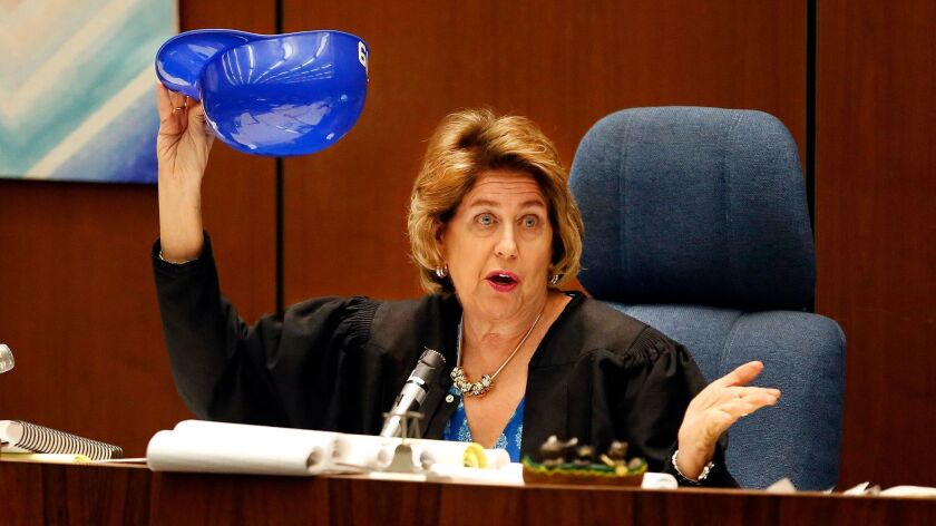 Judge Kathleen A. Kennedy picks a number from a souvenir Dodger helmet to select a replacement juror in the Grim Sleeper murder trial last year.