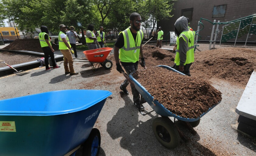 Corey Givens, 30, joined by other men spread seven truck loads of wood fiber playground chips at Baraga Park in Chicago, Thursday, May 17, 2018. American cities accounted for about 96 percent of the country's job growth in 2017 as they added nearly 2 million new jobs, according to the latest annual report from a bipartisan coalition of mayors.