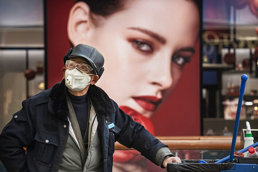 A worker wears a protective mask in a nearly empty shopping area Feb. 25 in Beijing.