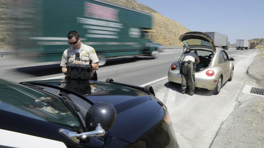 Los Angeles County Sheriff's deputies from a anti-trafficking team search a vehicle on the 5 Freeway in July. A Times' analysis of the team's stops found Latino drivers are stopped and searched far more often than other races.