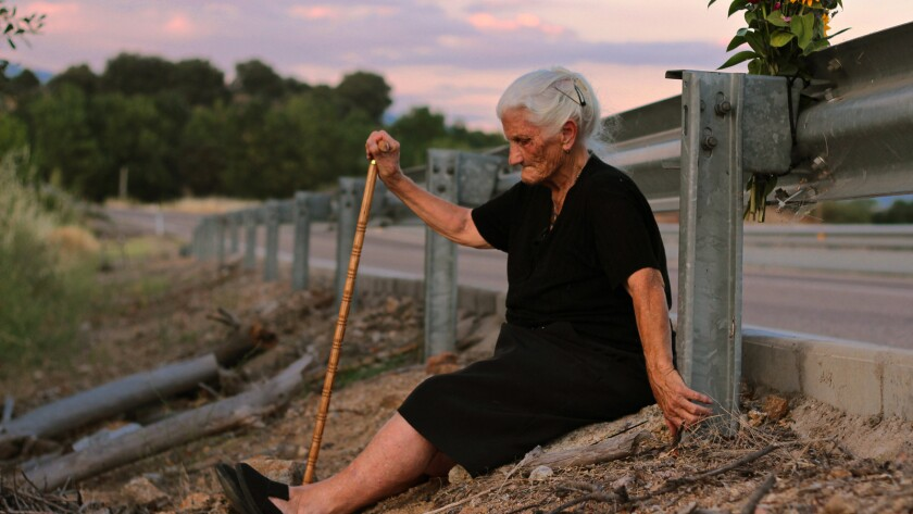 María Martín sits by the road which covers the mass grave containing her mother's remains in a scene