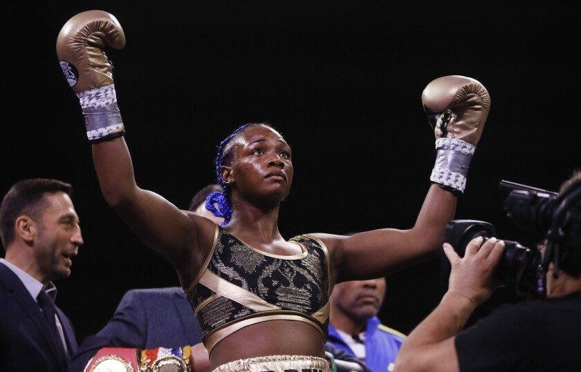 Claressa Shields raises her hands in boxing gloves in the ring.