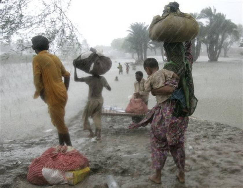 A Pakistani family displaced by floods prepares to cross a flooded road as the rain falls, in Shah Jamal village, Muzaffargarh district, Punjab Province, Pakistan, Saturday Sept. 4, 2010. More than 3 million people have yet to receive desperately needed food aid, according to the U.N., and the Pakistani government says nearly 1 million people have received no help of any sort. (AP Photo/Aaron Favila)
