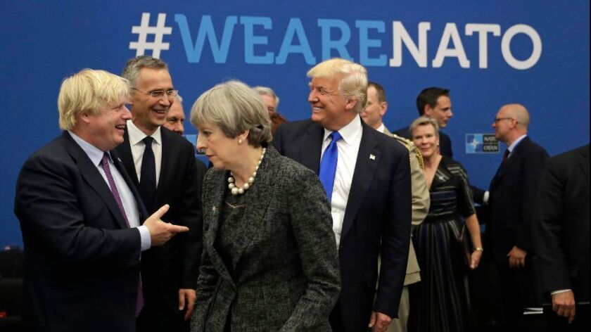 At the 2017 NATO summit in Brussels, President Trump jokes with British Foreign Minister Boris Johnson as British Prime Minister Theresa May walks past. Johnson resigned on Monday to protest May's Brexit policy.