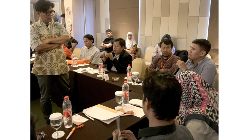 """Huda Noor Ismail, left, leads a conference at a hotel in Jakarta. The """"formers"""" are in the front row"""