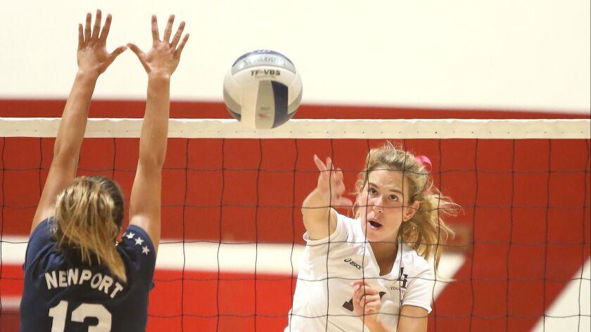 Laguna Beach High's Piper Naess puts the ball away for a kill past Newport Harbor's Jasmine Amirie