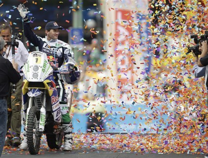 Spain's Marc Coma waves from his KTM bike during the symbolic start of the Argentina Dakar Rally 2010 at the obelisk in Buenos Aires, Friday, Jan. 1, 2010. Racing for the first stage of the 2010 edition of the Argentina-Chile Rally Dakar starts in the city of Colon on Saturday, and the rally runs through Jan 17 in Argentina and Chile. (AP Photo/Eduardo Di Baia)