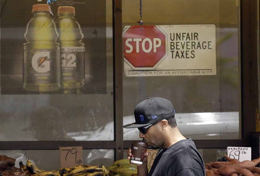 In this July 7, 2014 photo, a man drinks out of a coffee cup as he walks under a sign opposed to taxes on sugary drinks posted in the window of Casa Thai Market in San Francisco. San Francisco and Berkeley are aiming to become the first U.S. cities to pass per-ounce taxes on sugary drinks. (AP Phot