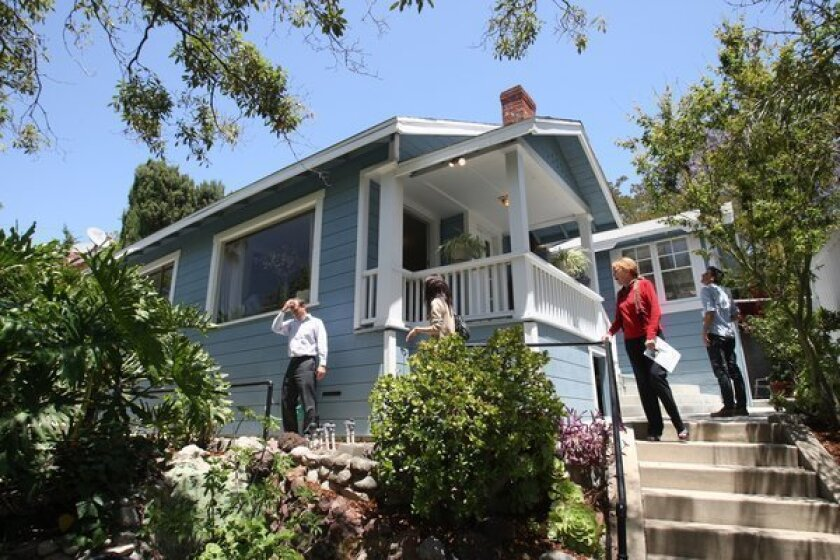 Buyers, Realtors and brokers look over a 1920s California Bungalow for sale in Highland Park.