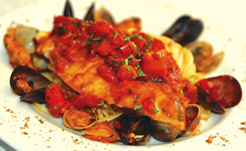Halibut Zia Luisa consists of a sizable halibut filet sautéed with mussels and clams, topped with tomato sauce and served over linguine at Osteria Romantica in La Jolla. Photo by Daniel K. Lew