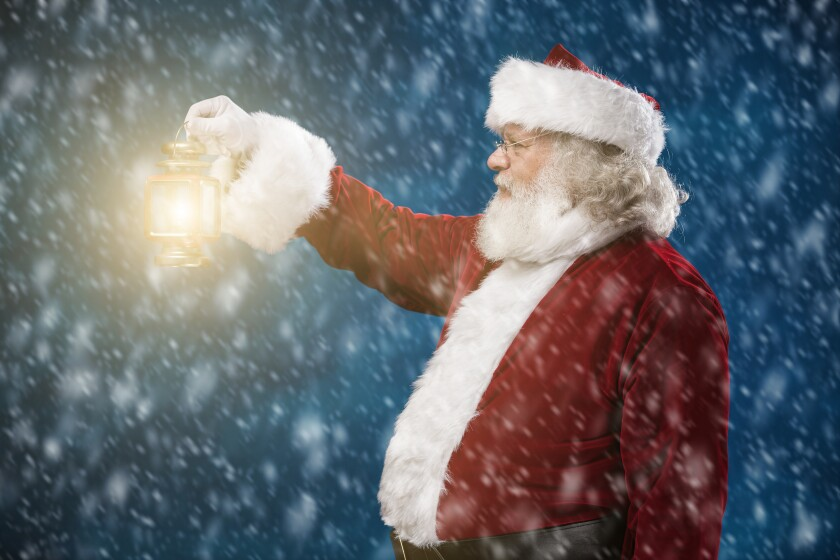 Santa holds a lantern in a snowstorm.