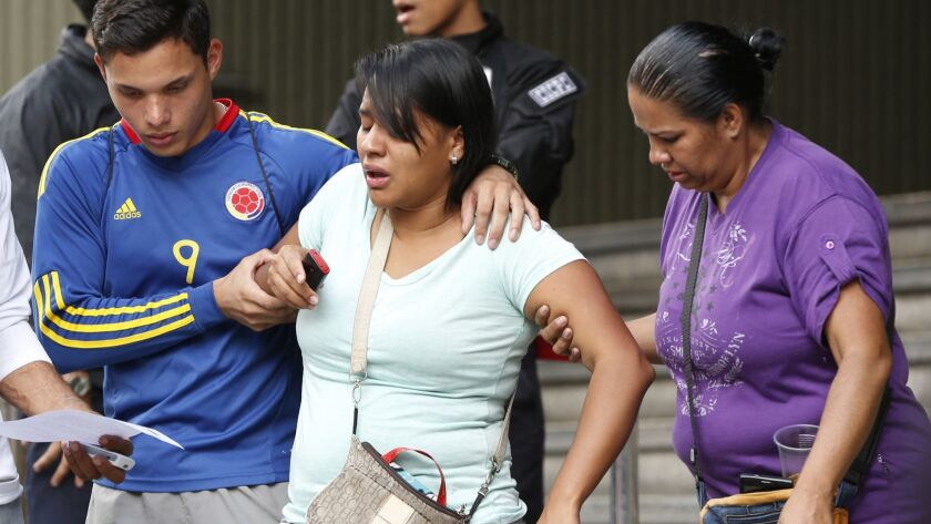 Barbara Barca, a survivor of the stampede at a crowded nightclub, is helped by relatives as they leave police headquarters in Caracas, Venezuela.