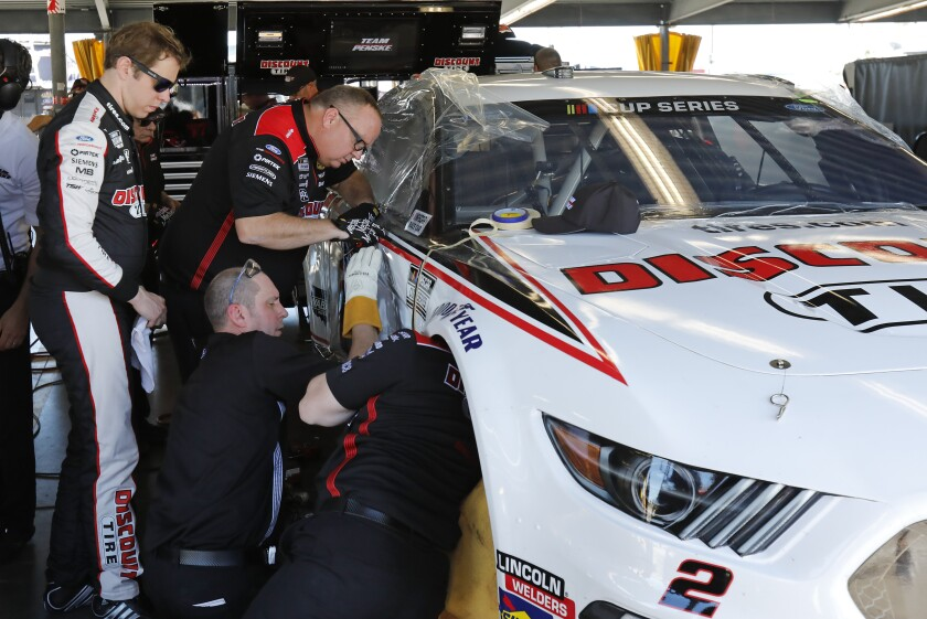 Brad Keselowski, left, looks over his car as his crew makes repairs after he wrecked during NASCAR auto race practice at Daytona International Speedway, Saturday, Feb. 8, 2020, in Daytona Beach, Fla. (AP Photo/Terry Renna)