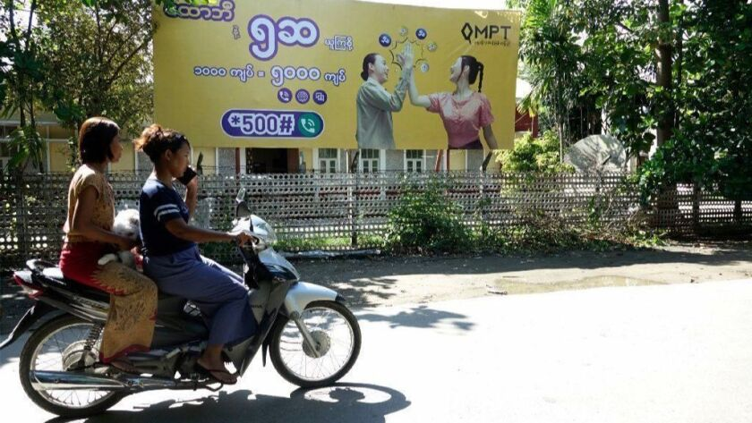 Two women ride past an ad for a cellphone company in Sittwe, Myanmar. The Myanmar government has temporarily shut down internet access in several conflict zones.
