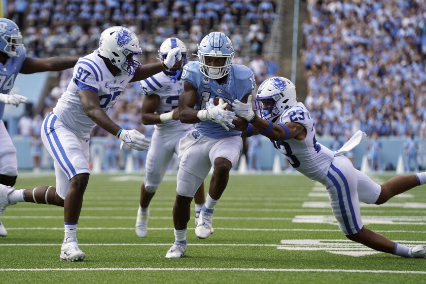 North Carolina running back Ty Chandler (19) runs while Duke defensive end Caleb Oppan (97) and Duke safety Lummie Young IV (23) reach to tackle during the second half of an NCAA college football game in Chapel Hill, N.C., Saturday, Oct. 2, 2021. (AP Photo/Gerry Broome)