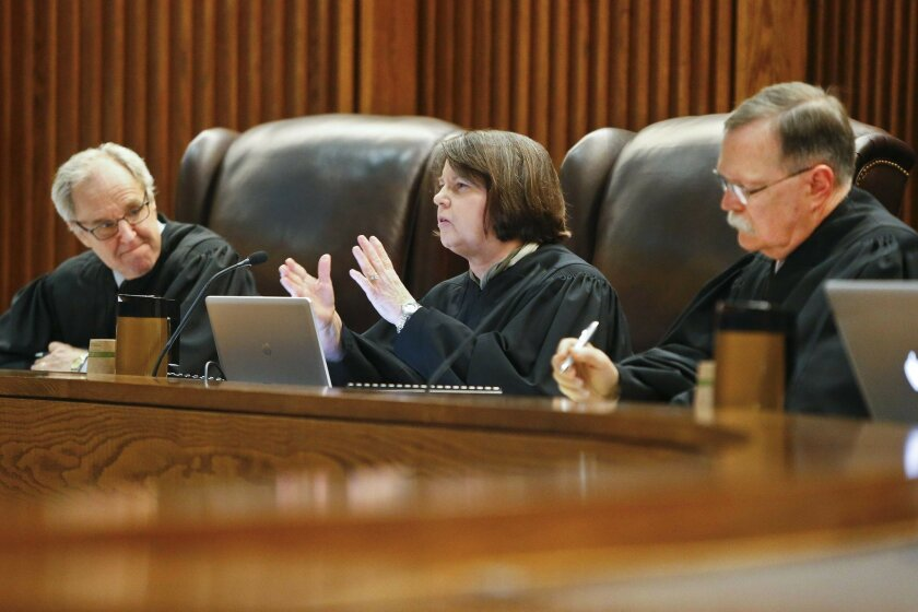 FILE - In this May 10, 2016 file photo, Kansas Supreme Court Justice Marla Luckert, center, asks a question to the state as they make their arguments in front of the Kansas Supreme Court, in Topeka, Kan. The judges are threatening again to close the state's public schools and has rejected some educ