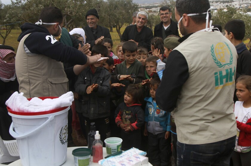Turkish aid workers with children at a refugee camp in northern Syria.