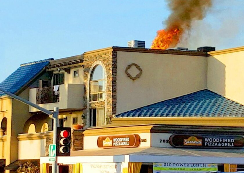 Flames reach the third-story roof of Sammy's Woodfired Pizza building on Pearl Street in La Jolla, Sept. 5, 2015. The restaurant is on the ground floor, but its kitchen hood (where the fire started) and vent extends to the roof. The fire was knocked out in 30 minutes.