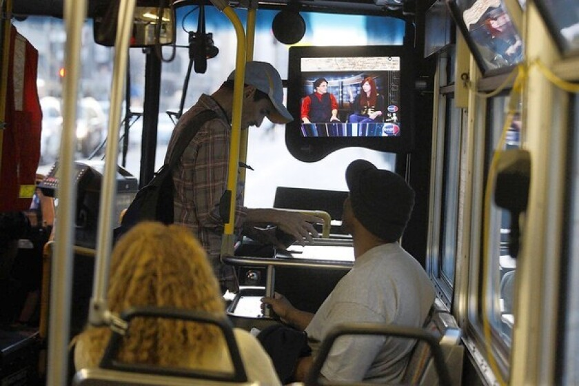 As riders ride a Los Angeles County Metropolitan Transportation Authority bus in downtown Los Angeles, television monitors show a daily newscast, produced by KNBC-TV Channel 4, on October 22, 2013 in downtown Los Angeles.