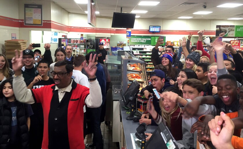 M. Faroqui, left, celebrates the sale of a winning Powerball ticket at a 7-Eleven in Chino Hills.