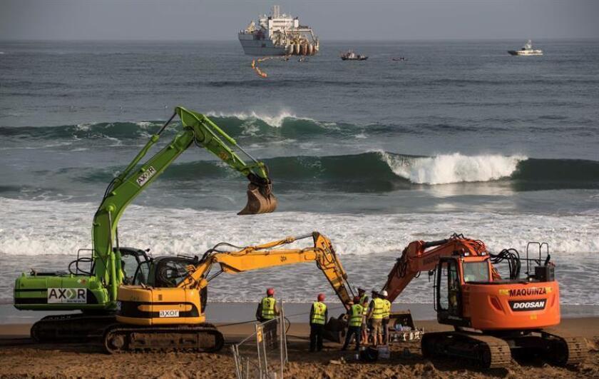 Fotografía de archivo que muestra a trabajadores mientras amarran a Marea, el cable submarino de fibra óptica construido por Facebook y Microsoft para unir ambos lados del Atlántico operado por Telxius (Telefónica), en la playa de Arrietara, en Sopelana (España). EFE/Archivo
