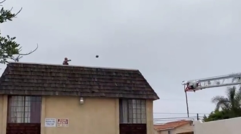 A man throws something off an apartment complex roof Wednesday in City Heights during what a more than 17-hour standoff