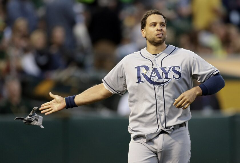 Tampa Bay Rays' James Loney tosses his glove after being ejected in the sixth inning of a baseball game against the Oakland Athletics, Saturday, Aug. 22, 2015, in Oakland, Calif. (AP Photo/Ben Margot)