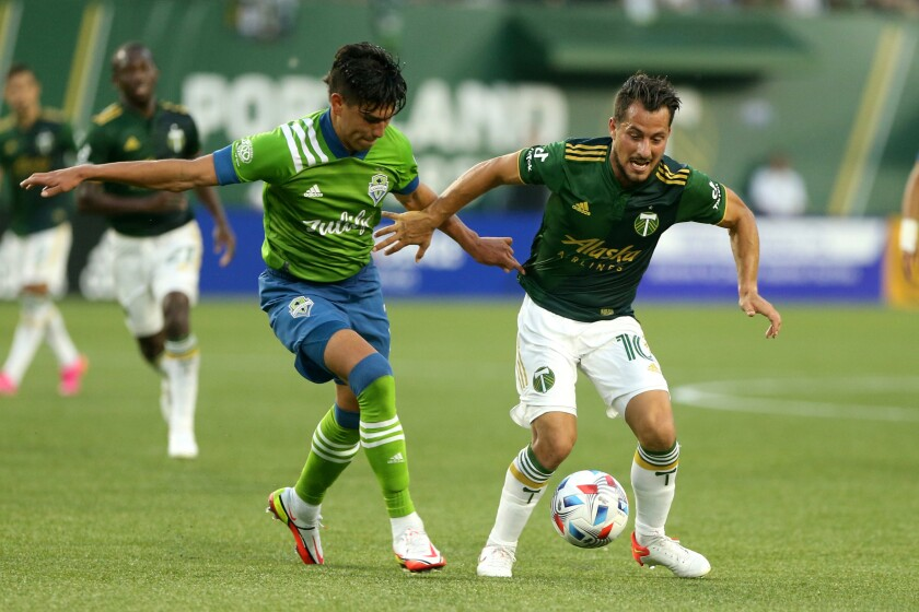 Timbers midfielder Sebastian Blanco, right, navigates around a Sounders defender as the Portland Timbers face the Seattle Sounders in an MLS match at Providence Park on Sunday, Aug. 15, 2021. (Sean Meagher/The Oregonian via AP)
