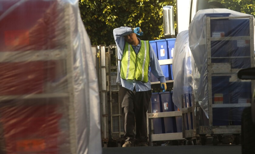A worker is surrounded by containers filled with biohazardous waste in Vernon.
