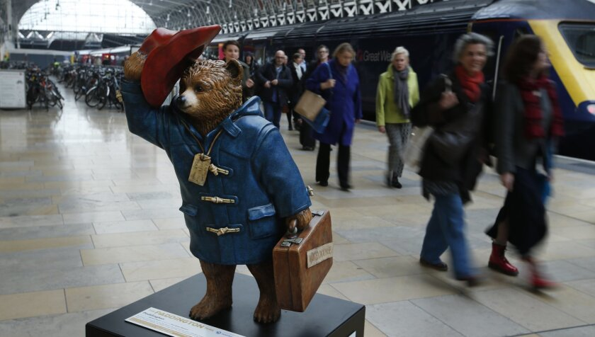 Commuters alighting from a train pass by a statue of Paddington Bear on the platform at Paddington r