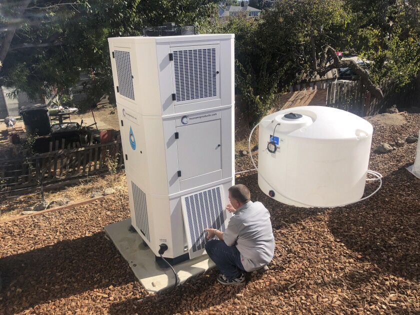 Ted Bowman, design engineer with Tsunami Products, installs a unit in homeowner Don Johnson's backyard in Benicia, Calif., Sept. 28, 2021. The recent invention can make water out of the air and in parched California, some homeowners are already buying the pricey devices. The air-to-water systems work like air conditioners by using coils to chill air, then collect water drops in a basin. (AP Photo/Haven Daily)
