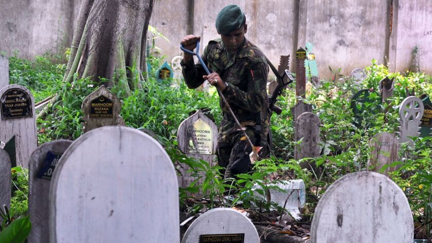 A Sri Lankan police special task force officer inspects a Muslim cemetery in Colombo on April 29.