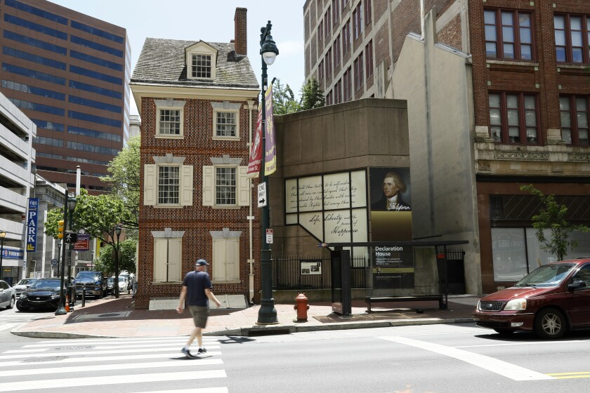 """In this June 30, 2020, photo, a man walks in front of the Declaration House in Philadelphia. Countless words have been written about the Declaration of Independence and Thomas Jefferson, but few about Robert Hemings, the slave who was on hand as Jefferson famously declared that """"All men are created equal."""" According to the National Park Service, Hemings is not included in the exhibit texts of the Declaration House, a reconstruction of the home Jefferson stayed in as a guest of the Philadelphia bricklayer Jacob Graff. (AP Photo/Matt Slocum)"""