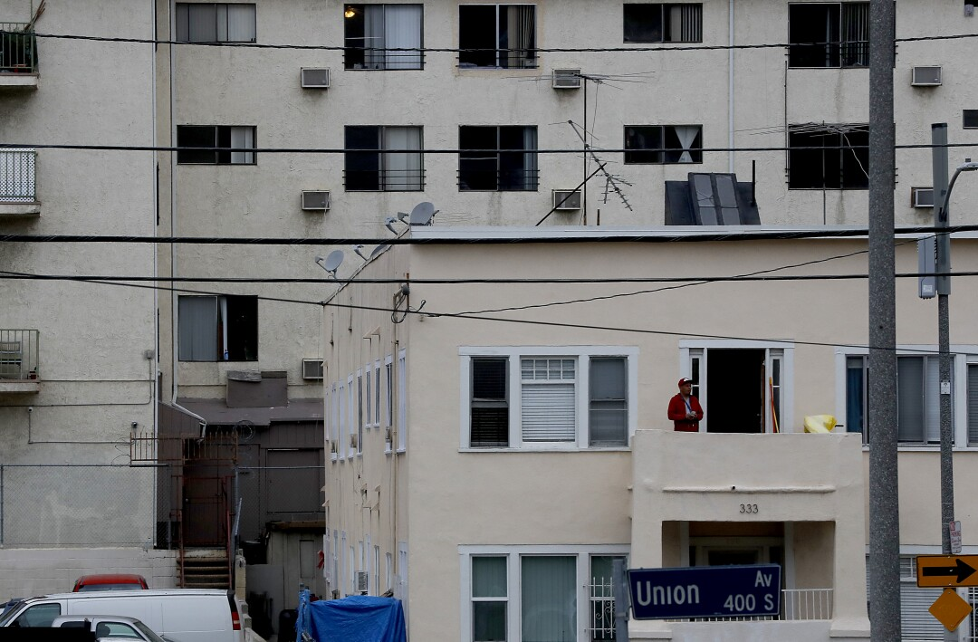 A man stands on a balcony of an apartment building on Union Avenue in the Westlake area of Los Angeles.