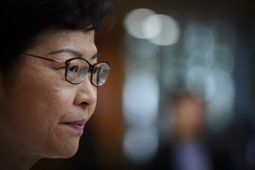 FILE - In this Nov. 26, 2019, file photo, Hong Kong Chief Executive Carrie Lam listens to a reporter's question during a press conference in Hong Kong. Protesters in Hong Kong got its government to withdraw extradition legislation last year, but now they're getting a more dreaded national security law. And the message from Beijing is: Protest is futile. (AP Photo/Vincent Yu, File)