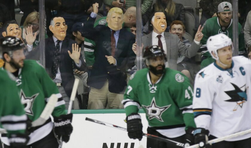 Fans in masks bang on the glass during the first period of an NHL hockey game between the San Jose Sharks and Dallas Stars Saturday, Oct. 31, 2015, in Dallas. (AP Photo/LM Otero)