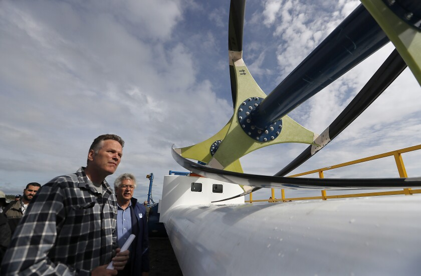 Alaska Gov. Mike Dunleavy looks at a hydroelectricity generator in Igiugig, a village in the state's southwest region. Residents of Igiugig and other remote areas are struggling with the effects of state government budget cuts from Dunleavy's line-item vetoes.