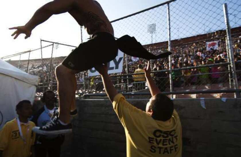 A fan tries to jump a fence at a Coliseum rave, the Electric Daisy Carnival, in June 2010.